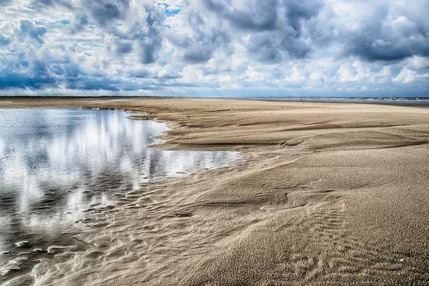 Schöner schuss des verlassenen sandigen ufers des ozeans unter dem bewölkten himmel Kostenlose Fotos