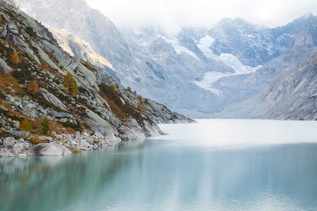 Schöner schuss des wassers umgeben von bergen unter einem bewölkten himmel Kostenlose Fotos