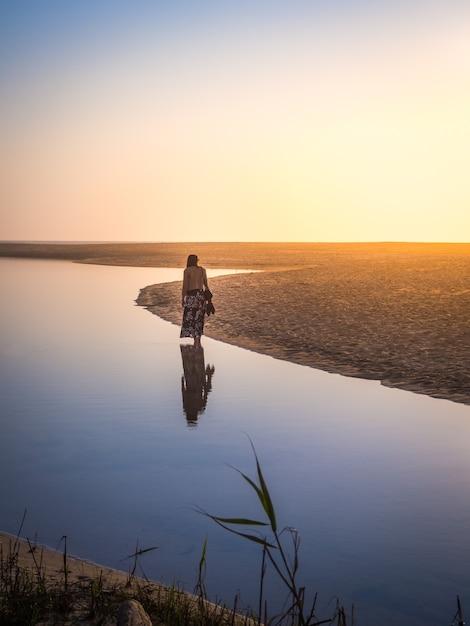 Schöner schuss einer frau, die am strand während des sonnenuntergangs geht Kostenlose Fotos