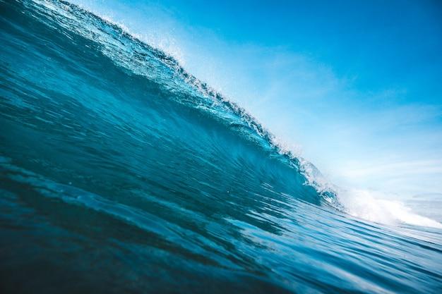 Schöner schuss einer welle, die form unter dem klaren blauen himmel nimmt, der in lombok, indonesien gefangen genommen wird Kostenlose Fotos