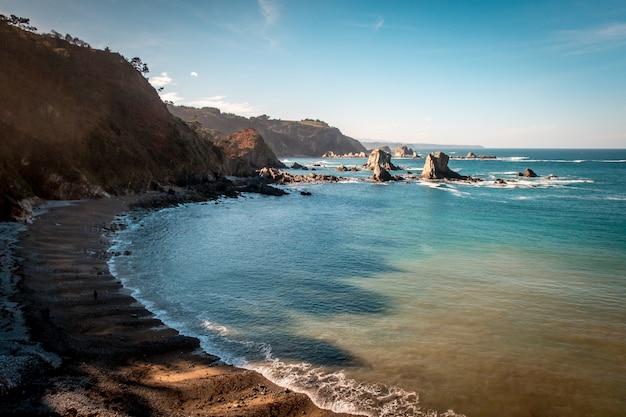 Schöner schuss eines ruhigen meeres mit hügeln auf der seite unter einem blauen himmel in asturies, spanien Kostenlose Fotos