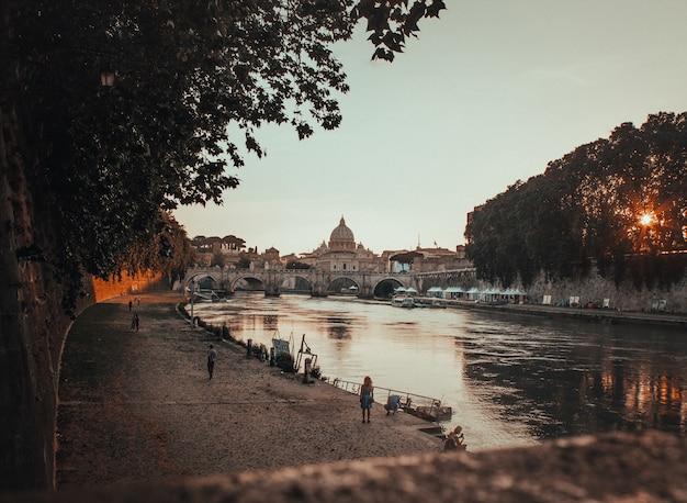 Schöner schuss eines schwarzen betonweges neben dem gewässer in rom, italien während des sonnenuntergangs Kostenlose Fotos