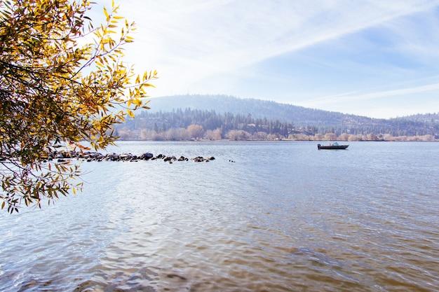 Schöner schuss eines sees mit einem boot, das auf ihm mit einem sonnigen himmel segelt Kostenlose Fotos