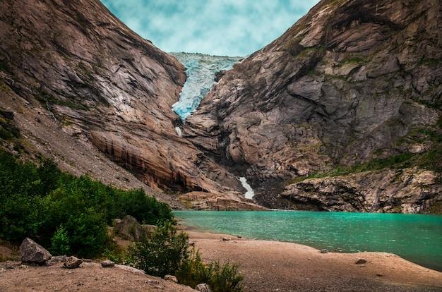 Schöner schuss eines sees nahe hohen felsigen bergen unter dem bewölkten himmel in norwegen Kostenlose Fotos