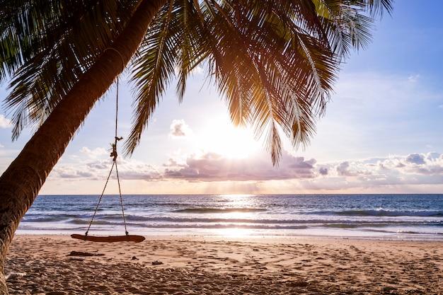 Schöner sonnenuntergang oder sonnenaufgang mit schattenbildpalme auf tropeninsel Premium Fotos