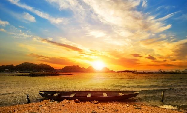 Schöner sonnenuntergang strandlandschaft mit einem boot Kostenlose Fotos