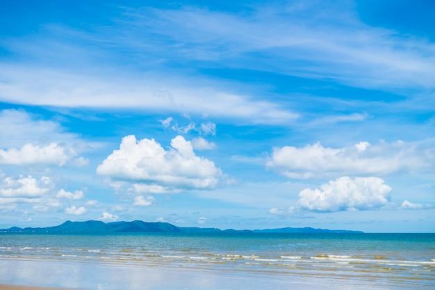 Schöner strand mit meer und ozean am blauen himmel Kostenlose Fotos