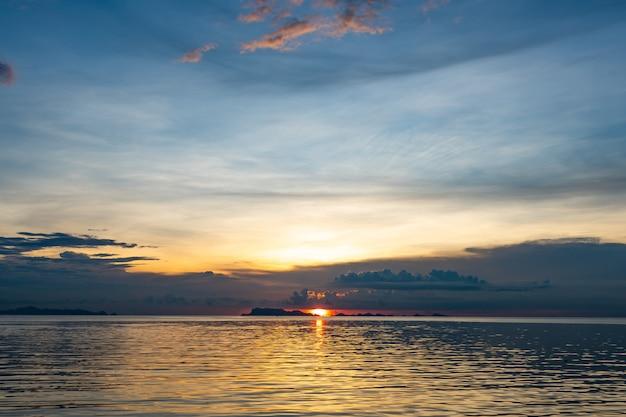 Schöner strandsonnenuntergang mit blauem meer und goldenem hellem himmel bewölken hintergrund Premium Fotos