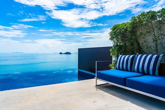 Schöner swimmingpool im freien mit seeozean auf blauem himmel der weißen wolke Kostenlose Fotos
