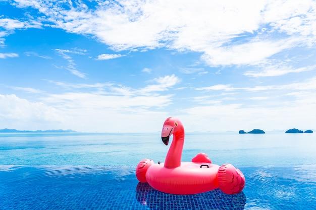 Schöner swimmingpool im hotelerholungsort mit flamingo schwimmen um weiße wolke des seeozeans auf blauem himmel Kostenlose Fotos