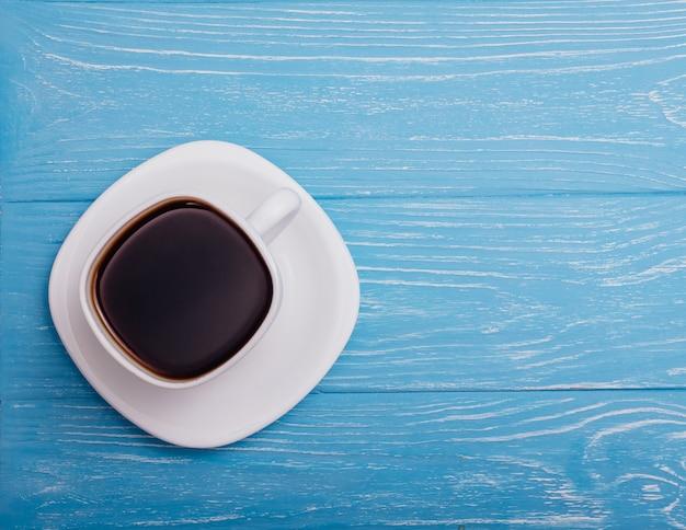 Schöner tasse kaffee auf einem blauen hintergrund Premium Fotos