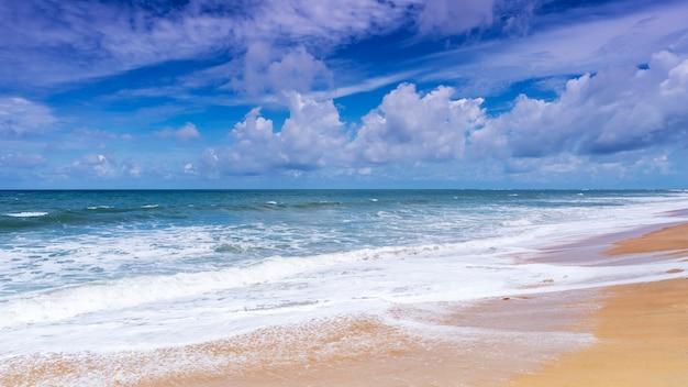 Schöner tropischer sandiger strand mit hintergrund des blauen ozeans und des blauen himmels Premium Fotos