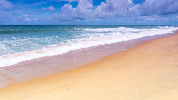 Schöner tropischer sandiger strand mit hintergrund und welle des blauen ozeans und des blauen himmels, die auf sandigem ufer zusammenstoßen Premium Fotos