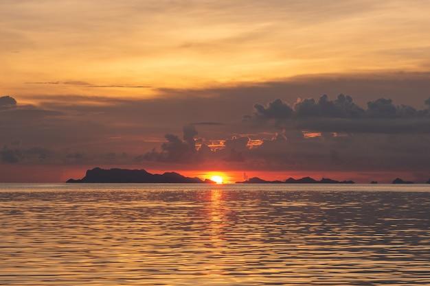 Schöner tropischer strandsonnenuntergang mit goldenem lichthintergrund Premium Fotos