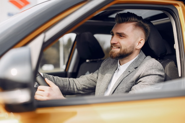 Schöner und eleganter mann in einem autosalon Kostenlose Fotos