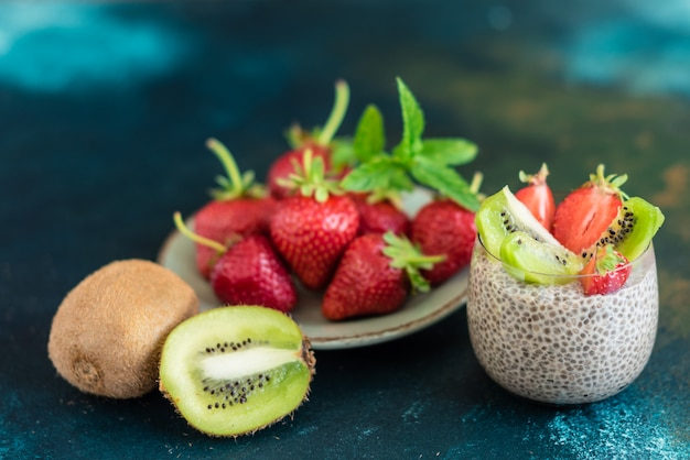 Schöner und leckerer nachtisch mit einer kiwi, einer erdbeere und samen eines chia Premium Fotos