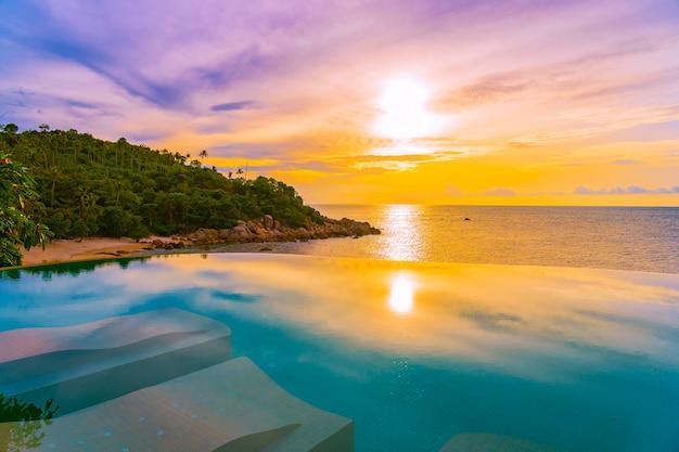 Schöner unendlichkeitsswimmingpool im freien mit kokosnusspalme um strandseeozean zur sonnenaufgangs- oder sonnenuntergangzeit Kostenlose Fotos