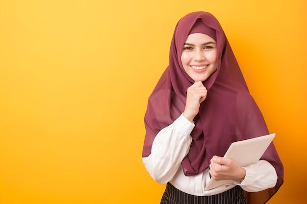 Schöner universitätsstudent mit hijab-porträt auf gelbem hintergrund Premium Fotos
