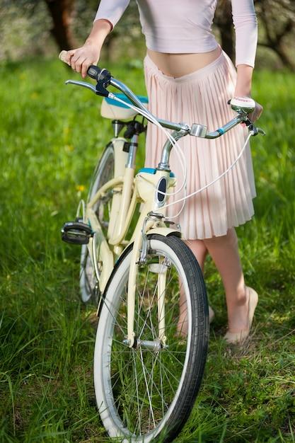 Schöner weiblicher radfahrer mit retro- garten des fahrrades im frühjahr Premium Fotos