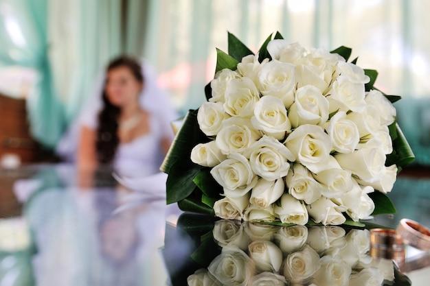 Schöner weißer brauthochzeitsblumenstrauß auf dem tisch Premium Fotos