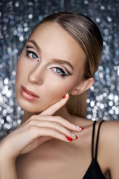 Schönes abendliches augenmake-up einer blonden frau auf einem glänzenden Premium Fotos