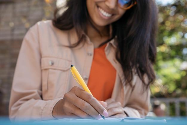 Schönes afroamerikanisches geschäftsfrauenarbeitsprojekt, stift haltend, notizen im notizbuch machend, am arbeitsplatz sitzend Premium Fotos