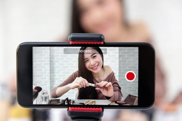 Schönes asiatinschönheit vlogger, das make-uptutorialvideo durch smartphone aufzeichnet Premium Fotos