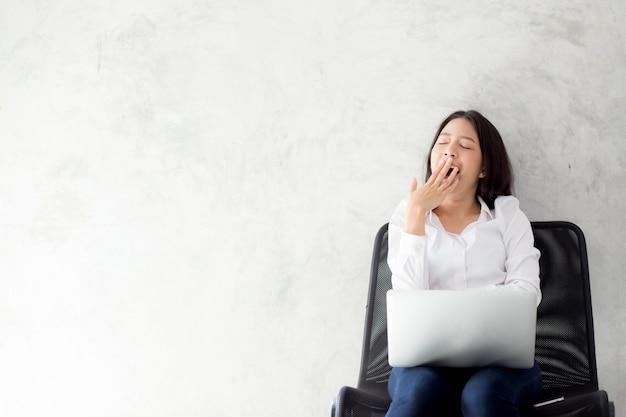 Schönes asiatisches frauengegähne des porträts an ihrem arbeitsplatz mit laptop-computer. Premium Fotos