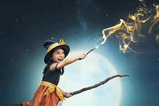 Schönes asiatisches hexenmädchen, das den magischen stab verwendet Premium Fotos