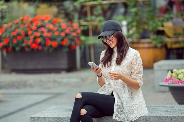 Schönes asiatisches junges frauenporträt unter verwendung des smartphones in der stadt Premium Fotos
