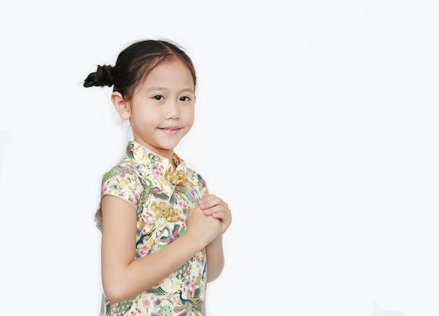 Schönes asiatisches kleines mädchen, das cheongsam mit lächelnder und willkommener geste trägt, die für glückliches chinesisches neujahr lokalisiert auf weißem hintergrund feiert Premium Fotos