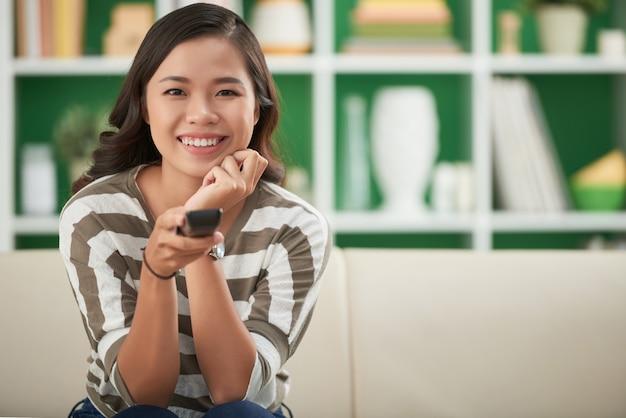 Schönes asiatisches mädchen, das zu hause auf couch sitzt und auf fernsehfernbedienung drückt Kostenlose Fotos