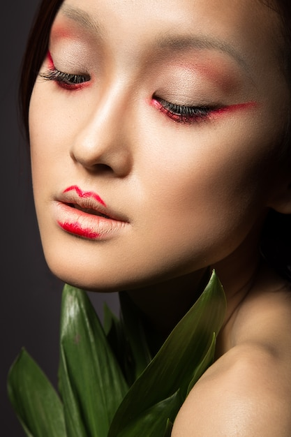 Schönes asiatisches mädchen mit einer hellen make-up-kunst in den grünen blättern. Premium Fotos