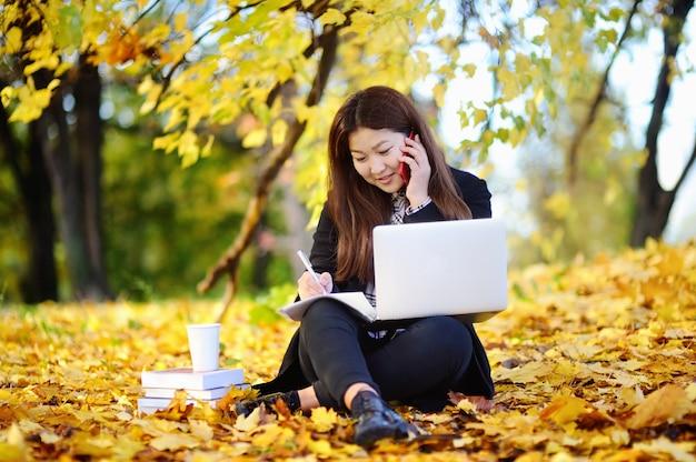 Schönes asiatisches porträt des studentenmädchens draußen. junge frau, die schönen sonnigen herbsttag studiert / bearbeitet und genießt Premium Fotos