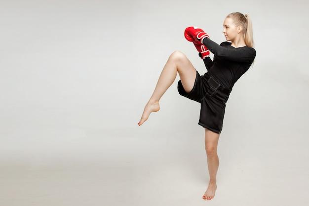 Schönes athletisches mädchen mit boxhandschuhen schlug hohen fuß. Premium Fotos