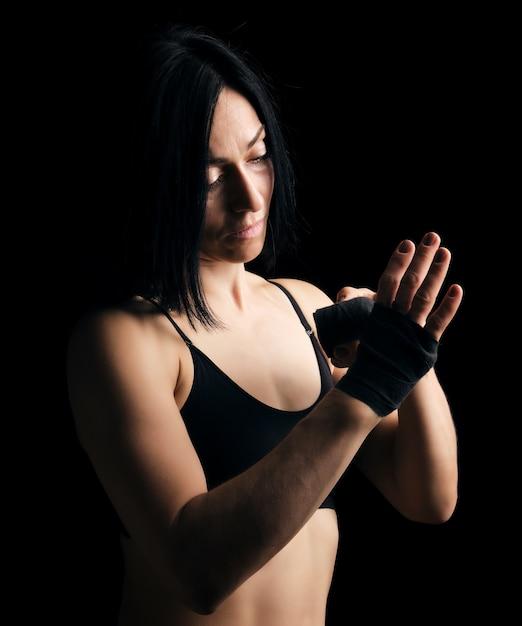Schönes athletisches mädchen mit dem schwarzen haar spult ihre hand mit einem schwarzen elastischen verband zurück Premium Fotos