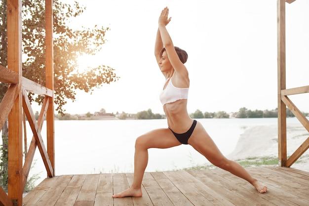 Schönes athletisches mädchen mit einem kurzen haarschnitt spielt sport auf dem see. kriegerhaltung im hatha yoga Premium Fotos
