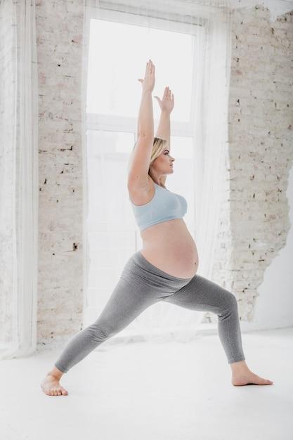 Schönes ausdehnen der schwangeren frau der seitenansicht Kostenlose Fotos