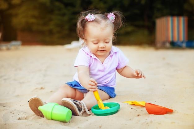 Schönes baby, das in den sandkastenspielwaren spielt. kindheit und entwicklung. Premium Fotos