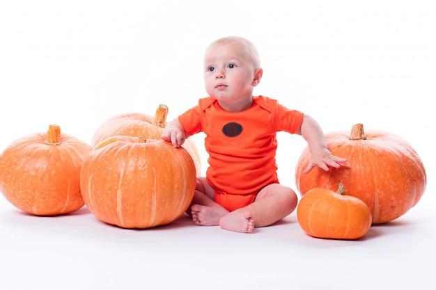 Schönes baby im orange t-shirt auf einem weiß sitzt Premium Fotos