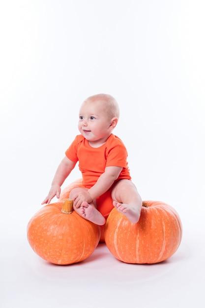 Schönes baby im orange t-shirt sitzen Premium Fotos