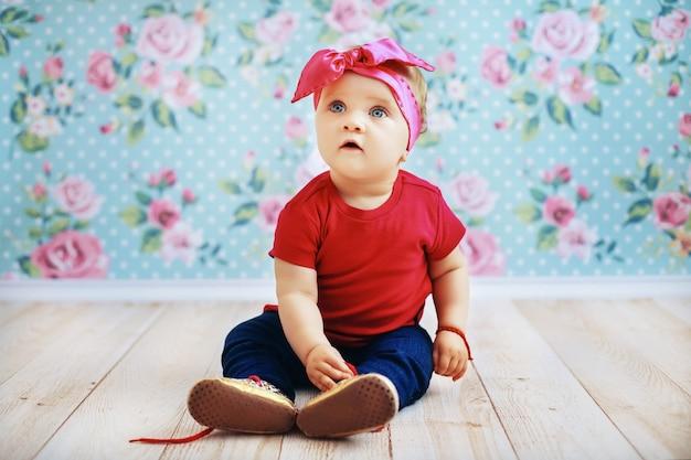 Schönes baby in einer rosa jacke und in jeans, die auf dem boden sitzen. erziehung. Premium Fotos