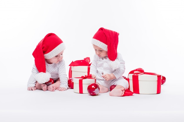 Schönes baby zwei in der kappe des neuen jahres und im weißen körpersitzen Premium Fotos