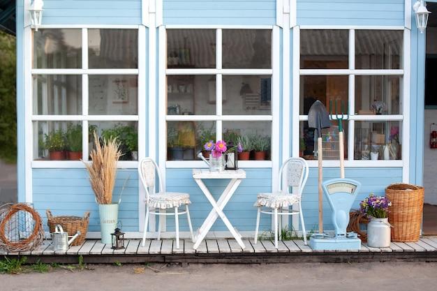 Schönes bauernhaus mit weidenkörben und grünen pflanzen auf der terrasse. weißer tisch und stuhl auf der veranda des hauses. Premium Fotos
