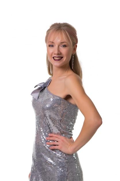 Schönes blondes mädchen, das auf einem weiß in den glänzenden kleidern, getrennt aufwirft Premium Fotos