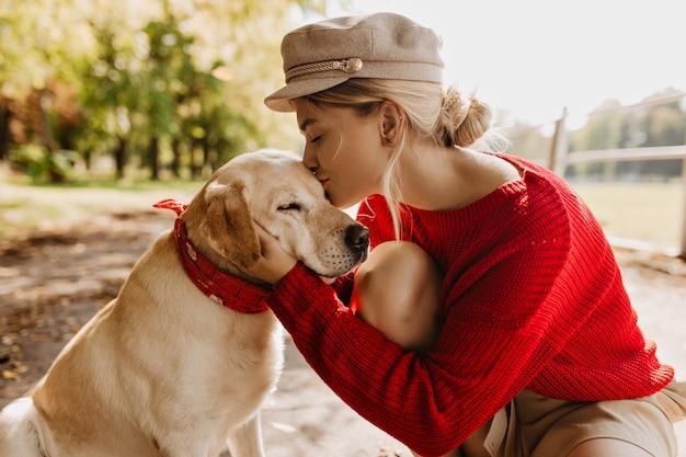 Schönes blondes mädchen, das ihren entzückenden hund im sonnigen herbstpark küsst. stilvolle junge frau im roten pullover und im trendigen hut, der zart das haustier hält. Kostenlose Fotos