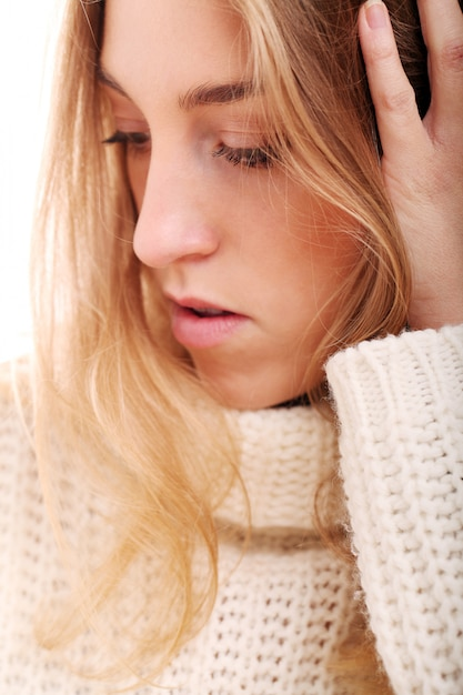 Schönes blondes mädchen in gestrickter strickjacke Kostenlose Fotos