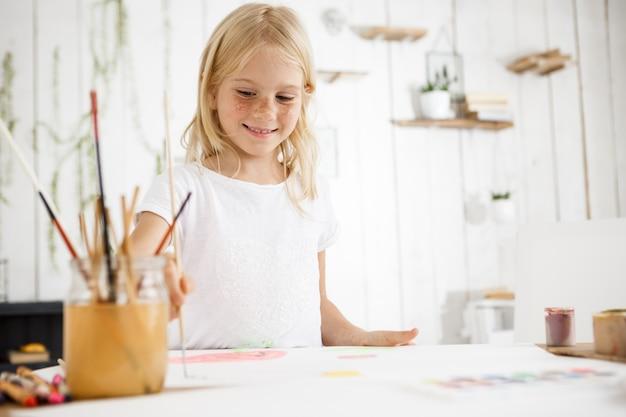 Schönes blondes mädchen lächelnd und freudig malendes bild mit pinsel Kostenlose Fotos