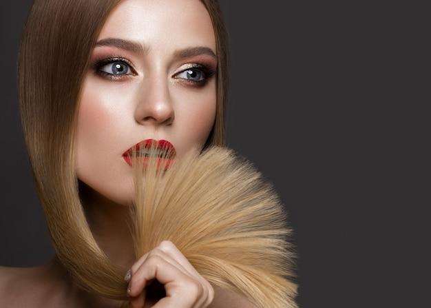 Schönes blondes mädchen mit einem tadellos glatten haar, einem klassischen make-up und roten lippen. beauty gesicht Premium Fotos