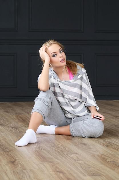 Schönes blondes sitzen auf bretterboden Kostenlose Fotos